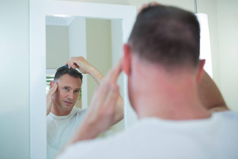 man-kämmt-sein-Haar-in-die-Badezimmer